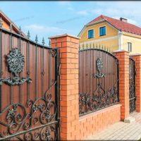 Кованый забор из профлиста с кирпичными столбами